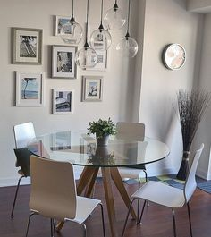 Dining Room decor ideas - small dining with round glass topped stable, modern style, hanging glass orb light fixtures and simple gallery wall   Apartment Therapy tour: Ken and His Belle of New York