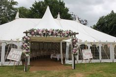 Our marquee: wonderful flower arch from Emma Webster, table plans using vintage frames and bunting from Beautiful Bunting