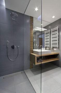 Z szarością glazury w tej łazience efektownie kontrastuje drewniana półka zintegrowana z blatem pod umywalką. Z tego samego materiału wykonano dekoracyjny pas przy lustrze. Ścianka mocowana dyskretnymi profilami wydziela strefę natrysku.