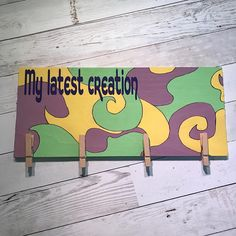 I love my stainless steel refrigerator, but I dont love that I cant put my kids artwork up on it because its not magnetic! So I came up with an alternate solution. This fun, bold plaque in purple, green, and yellow has four clothes pins mounted on it to hold either four separate pieces or you can use two clothes pins per piece to make sure it doesnt spin if it gets bumped into, possibly by the owner of said artwork. Each plaque is custom made and therefore may have a different pattern from…