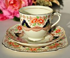 Tuscan vintage bone china Imari style teacup, saucer and tea plate trio. A pale clotted cream colour with a hand painted over transfer pattern featuring a delicate floral border in taupe, lime green and orange. A central band of cobalt blue and lime green deco motifs edged with gold and a taupe fingerprint pattern lower band. The Imari style patterns were intended to shine in candlelight. All pieces have 22 Kt gold gilded rims and the teacup has a gold band inside the cup, at the base and on…