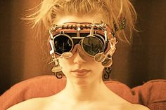 The 'Mother' of the Phreak Show, Millie Lemar-Maestro is a person with albinism. She suffers from the poor eyesight often caused by this condition. Her husband, Phineas, created her a pair of goggles (much less fussy than these) which allow her to overcome this hindrance.    Another pair--outfitted with GPS technology--is used by the resident Pinhead for the Troupe's navigation.