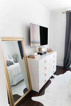 WANT A TV IN ROOM ! Chic bedroom features a flatscreen TV atop a white Ikea Malm Dresser adorned with gold ring hardware next to a gold leaf leaning mirror alongside a metallic cowhide rug. Decoration Inspiration, Room Inspiration, Decor Ideas, Design Inspiration, Black White Bedrooms, White Gold Bedroom, White And Gold Bedroom Furniture, Ikea Bedroom Furniture, White Rooms