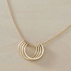 This is the smaller version of one of our most popular necklaces, the Honey Petals. We love how it dances around on your neck as you move about your day, and we think you will too! Four circles are hammered and stacked on a delicate cable chain - pendant measures