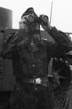 SS-Sturmbannführer Christian Tychsen, commander of II./SS-Panzer-Regiment 2 of the Das Reich Division, photographed during the Kursk battles in July 1943 as he takes a little pause for smoking and drinking between heavy combats. He is wearing the tanker's one-piece camouflage suit.