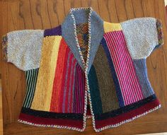Gather a colorful array of stash and scrap yarns and knit a versatile statement piece! Begin with a seed stitch rectangle followed by a series of welts on the back. The sides and fronts are knit sideways in garter stitch with simple v-neck shaping. Then, work two rectangles for the shoulders and tapered seed stitch sleeves. Garter stitch short rows form the collar and another garter stitch rectangle forms the bottom band, all outlined in I-cord. Upon completion, you have a fun short sleeved…