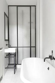 Une salle de bains séparée par une verrière avec meuble sous vasque rétro et baignoire ilot