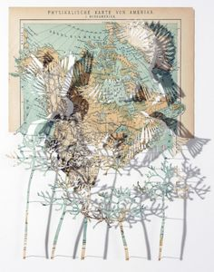 Claire Brewster    Cut outs from maps. I like how the original map has been kept intact and placed behind the bird-cutouts but behind the flower-cutouts there is white space.