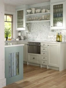 Modern kitchen design with light hardwood floors and off-white as a dominant colour. Glass-face cabinets. Modern with a classic feel and country cottage elements.