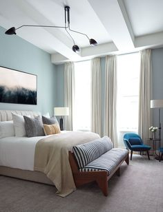 """We struck a balance between making the space feel masculine, while still giving it the ability to appeal to a woman,"" notes Sanders of the master bedroom. The walls are bathed in Pale Powder by Farrow & Ball; a bed from Consort cozies up to a bench from Sabin. Over the bed hangs a dreamy art piece by Brian Merriam."