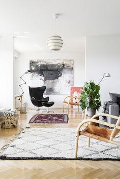 Designklassikot, taide ja rauhalliset värit ovat pääosassa avarassa ja tyylikkäässä kerrostalokodissa. Tavaraa ei ole liikaa.