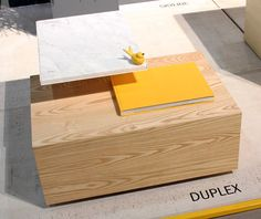 The bi-level Duplex table from Phase Design has a rectangular wood part below and a smaller square marble piece that sits in a metal base above.