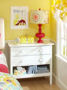 "All Dressed Up ""Next to the bed, a small flea market dresser finds new life as a nightstand. The top drawer offers charging capabilities for cell phones and electronics, while the bottom drawer was removed, leaving a display compartment. Outfitted in the same fabric as the bed linens, a tissue holder adds a splash of youthful character in an unexpected place."""