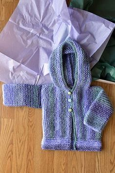 This cardigan is worked from side to side. The cardigan fronts and hood are worked in one piece, and then the sleeves and back are worked separately. Once seamed, the bottom band is picked up and knit along the bottom and the front is edged with crochet which also forms the button loops. Designed by