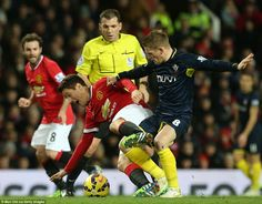 Steven Davis (right) tussles for the ball with substitute Ander Herrera (left) of United i...