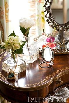 The kidney shaped vanity with a round antique mirror beckons with beauty. - Traditional Home ®/ Photo: John Bessler / Design: Heather McManus