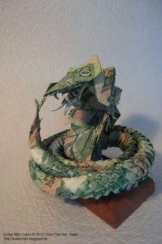 適逢蛇年,香港摺紙設計師 Kade Chan 以18張「青蟹」摺出青蛇,寓意「蛇年實發」! 青蛇一共用了18小時以及18張10元紙幣製作,實物約有10cm高, 製作一絲不苟,眼睛,牙齒以致鱗片等都相當精細。  Dollar Bills Cobra © Chan Pak Hei , Kade 2013 http://kadechan.wix.com/portfolio