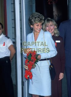 HRH PRINCESS DIANA, THE PRINCESS OF WALES.At a Sexual Heath Clinic in London, England, .1st December 1994..royal Lady Di half length pale blue jacket skirt suit black bag gold chain strap red flowers.CAP/HT.©Hugh Thompson/Capital Pictures