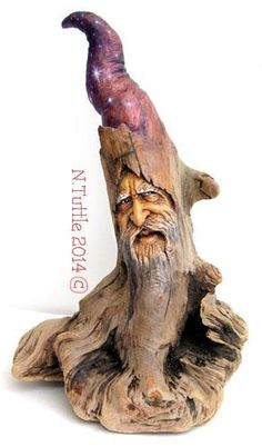 """""""A Wizard's Way""""    10¼ inches tall and 7 inches across his greatest width.  Carved from a single piece of Oregon driftwood, this   wizard is a freestanding sculpture but is also drilled in   back to be hung on a wall. ''I've added some color using   stains made from oil paints''.  Signed and dated:   N. Tuttle 9/21/14"""