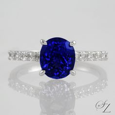 An enchanting, deep blue oval Tanzanite sits between a trail of pave set Diamonds... what more do you need?