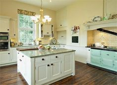 Creamy yellow and white kitchen with marble counters and mint green Aga