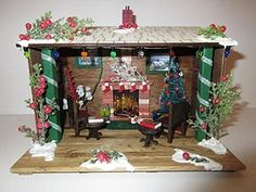 Miniature Christmas Winter Diorama OOAK Fairy Garden Accessory. This miniature OOAK rustic Christmas Hut/diorama has all the warm comforts of home. The hut is made of various wood, stained, painted, glued and sealed. Inside you will find a warm faux fire going in the fireplace where the stockings are hung. There is small carpet in front of the fireplace with a Christmas book, a cup of cocoa and a plate of cookies for Santa. Unless the fairies get to them first! The walls are adorned with...