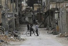 Men chat near buildings damaged by what activists said was shelling by forces loyal to Syria's President Bashar al-Assad in Daraya, near Damascus February 2, 2014. REUTERS/Omar Abu Bakr/File Photo