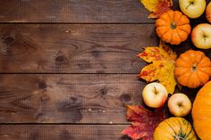 Apples, pumpkins and fallen leaves on wooden background. Copy space for text. Halloween, Thanksgiving day or seasonal background. Design mock up.