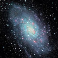 Eight million light-years away lies galaxy NGC 2403. Spanning nearly 50,000 light-years in diametre, the galaxy displays its incredible spiral arms with hot young stars in blue and glowing star formation regions in red. Credit: Canada-France-Hawaii Telescope/Coelum