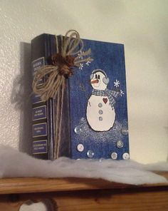 Book painted with snowman. (I painted several of these to give away as gifts!) A sponge (and a very light touch with the white paint) was used to create the snow texture.  As this one was made for someone who sews, buttons were added at the bottom.  A jute twine bow was tied around the cover. This might be a great project if your library receives a lot of donated Reader's Digest condensed sets and they do not sell at the book sale. :-)