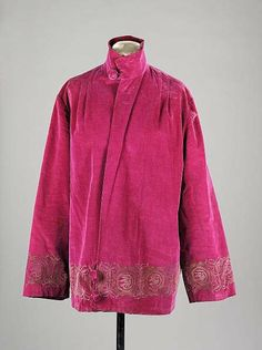 1920's. A raspberry silk velvet jacket with Renaissance inspired border of scrolls and birds stencilled in metallic pewter along the lapels, hem and cuffs.