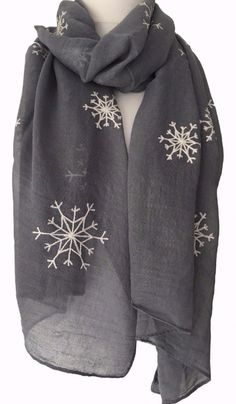 A grey scarf with a cream embroidered style snowflake pattern Soft light weight cotton blend fabric Measurements approx 72 inch 183 cm in length