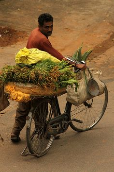 """""""Door to door sales of fresh vegetables, this seller is a a regular to our neighborhood for years, early morning he takes round to the residential lanes selling fresh vegetables he sources from wholesale markets and makes his living, many homes get used to buying from him and saving their trips to markets.""""  Photo by rajesh_dangi on Flickr."""