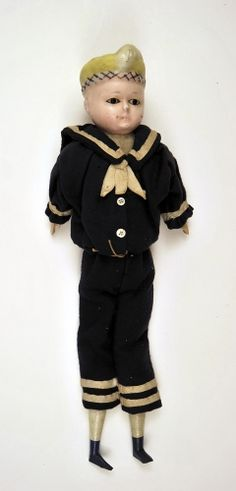 "1880 Doll Medium: wax, composition ""Pumpkin"" head boy doll with moulded yellow hair, brown inset eyes. Made of thin wax over composition, wooden limbs, blue painted boots, rag body. Wearing blue serge sailor suit."