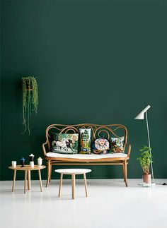 Luscious Emerald green wall and simple wooden furniture are definitely a match made in interior heaven! The hanging plant is also a very welcome addition.