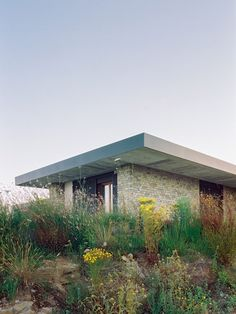 """Different-hued chunks of stone from the nearby town of Alberese have been used to create what the architects describe as a """"thick skin"""" around the exterior of the home. Metal Shutters, Black Shutters, Composite Flooring, One Storey House, Architectural Section, Open Plan Living, Mexico City, Contemporary Architecture, Verona"""