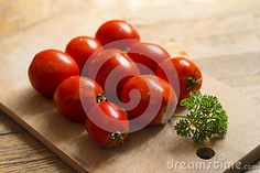 Red Tomatoes And A Sprig Of Parsley On A Wooden Cutting Board. #tomato #tomatoes #red #redfood #vegetables #cute #tasty #cooking #photography #dreamstime #lovely