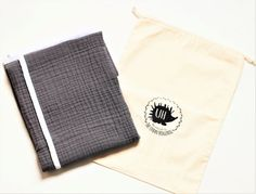 This luxury baby blanket will make a perfect gift for any baby. Handmade by us with only high quality, organic and breathable materials to keep children warm without overheating. Materials: 100% three-layer organic muslin (cotton), with 100% organic white bamboo border.  Measures: 94 x 74 cm approx. (37 x 29).  Colours: Dark grey and white  The blanket comes in our handmade bag for great presentation!  The blanket is ready to ship.  Product is 100% handmade in Ontario, Canada.  Washing…