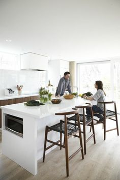 ikea center island in the kitchen with chic clear parquet and dark wood bar chairs
