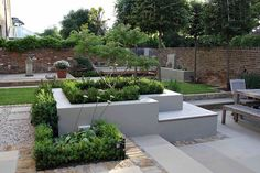 white rendered raised beds, terraced garden seating/dining areas with stone pavers set into gravel