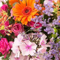 Bouquet rond festif et aérien, composé de roses et fleurs variées aux teintes orange et fuchsia. Accompagné de son vase offert4.