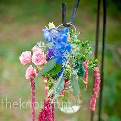 Mson jars hanging from shepherd's hooks.