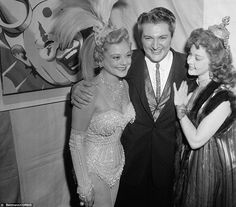 Party animals: Skating star Sonja Henie, left, welcomes pianist Liberace, center, and actress Susan Hayward, right, to her star spangled party at Ciro's nightclub in February 1955
