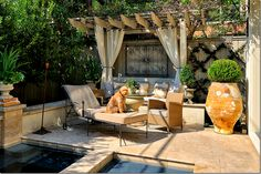 second courtyard, off the family room, is where the swimming pool is.  To one side is a draped pergola that creates an outside room