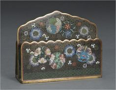 A cloisonné enamel letter stand Meiji period Two scalloped-edge open compartments bracketing a taller center piece with a scalloped triangular upper section, the exteriors decorated with scattered floral roundels and blossoms in brightly colored enamels on a black ground with a dense spiral pattern (losses to the base).
