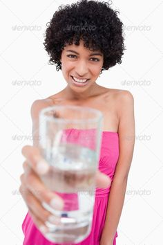 Teenager holding a glass of water in front of her while smiling ...  20-24 years, Focused Shot, Looking At Camera, One Person, Studio Shot, Young Women, beautiful, celebrate, celebrating, celebration, copy space, cute, drink, emotion, festive, front view, glass, half length, happiness, happy, hold, holding, ice, isolated, liquid, looking, mixed-race person, offering, pretty, smile, smiling, standing, water, white background