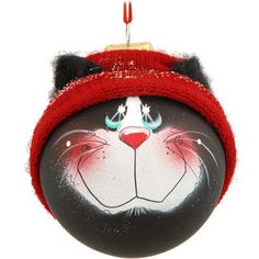 """Featuring the heart-warming artistry of Pam Chatley, this purr-fectly adorable black cat SockHead™ glass ornament is artfully infused with home-spun charm.  Our cat's artfullly hand-painted face is composed of two soulful eyes, a button nose and a whimsical grin all framed by a festive red knit hat that allows his two pointy ears to peek through. Coming ready to hang with a red ribbon, this 3¼"""" round frosted glass ornament is paws-atively darling! ©Chatley. Made in the USA.B..."""