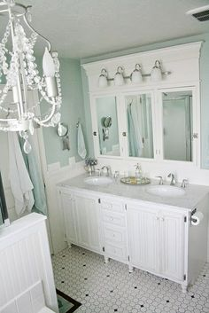 Multi light mounted to decorative board over multi mirror vanity.