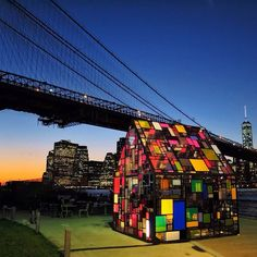 Brooklyn Bridge Park, New York City, New York — by gavvykins. Stained glass house by Tom Fruin at Brooklyn Bridge Park at sunset.