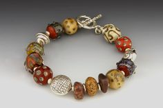 Race Point Terra Cotta Bracelet by Dianne Zack. Part of the Race Point Series, this bracelet features beach stones gathered from the National Seashore at Cape Cod. Handmade glass beads have silver leaf and tiny dots of clear glass on the surface. The composition is rounded out with fine silver beads, signature tag, and toggle clasp. The beads are strung using a 49-strand braided and coated metal wire for strength. Some variation in shading and bead sequence will occur, but each piece will…